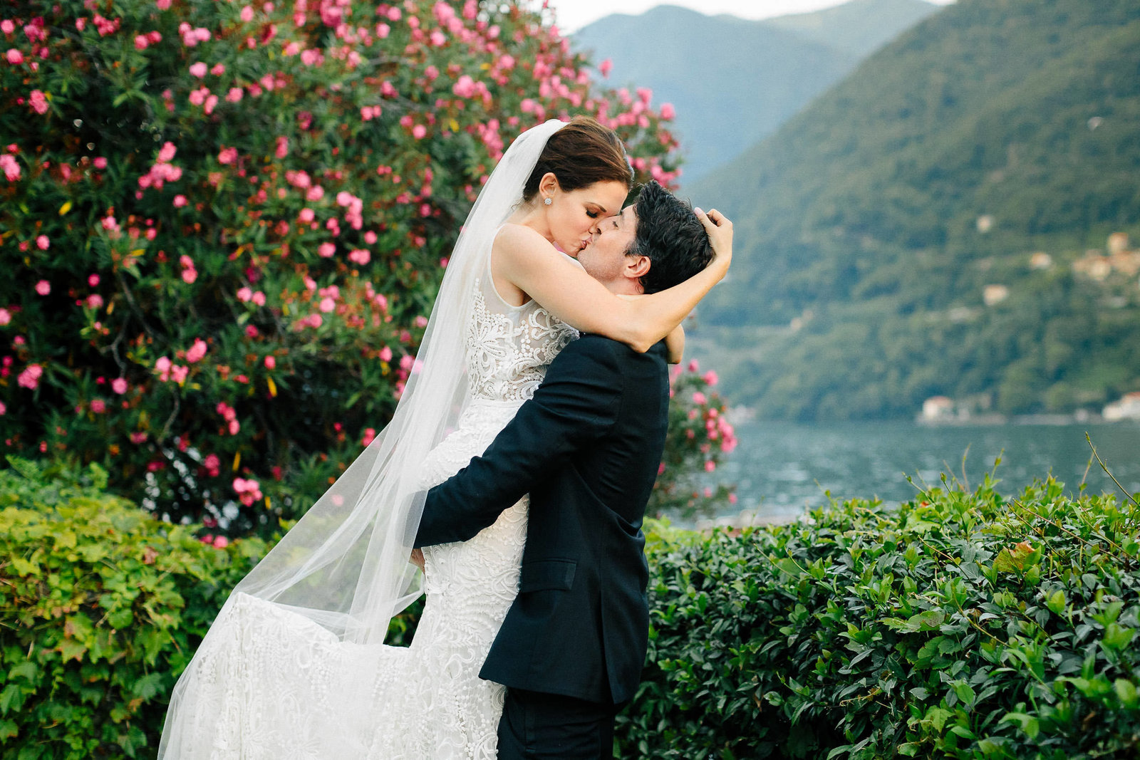 bride and groom kissing and hugging in front of pink flowers