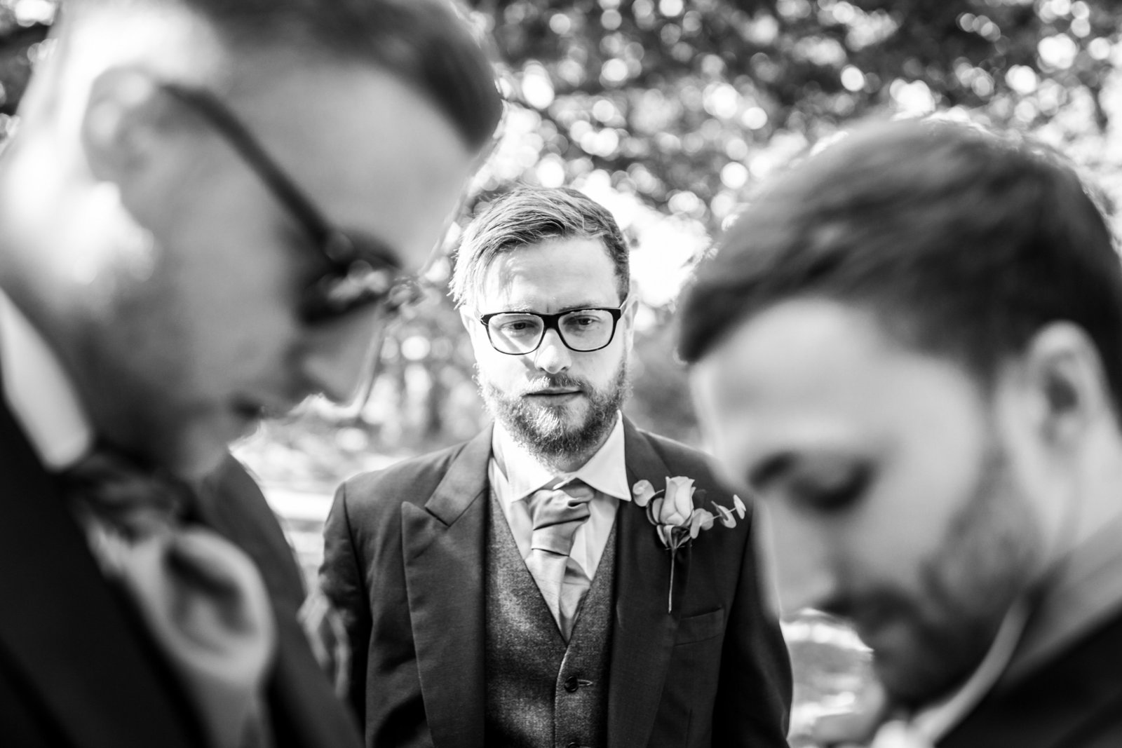A groomsman helps the groom put on his buttonhole whilst another groomsman watches outside a church in Norfolk.