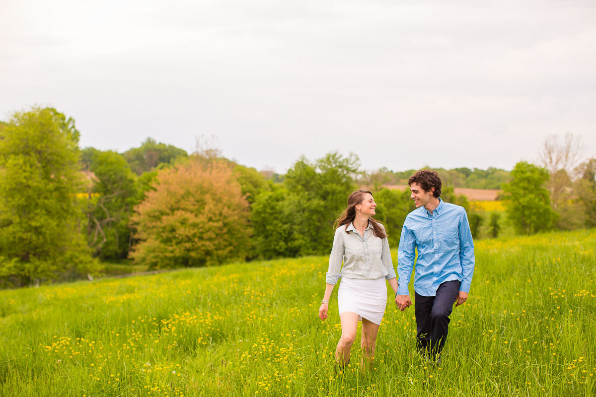 couple walking in a field for engagement photos in maryland