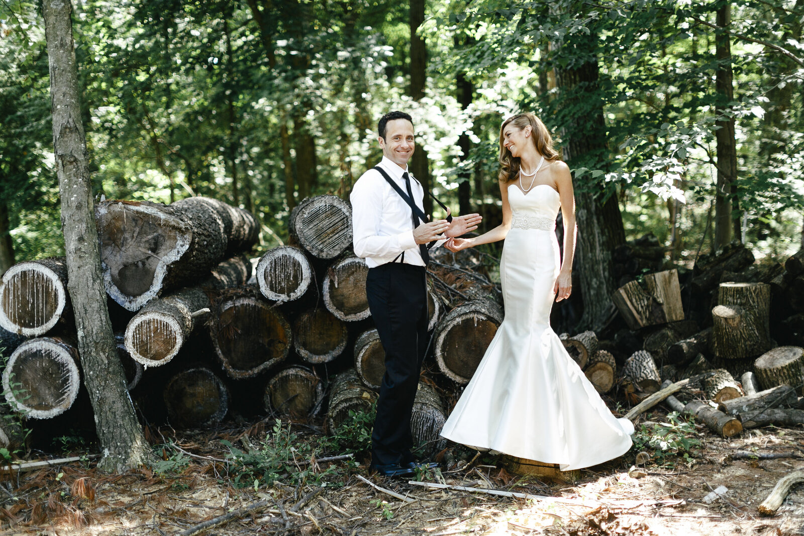 bride and groom with suspenders on farm with woods pile