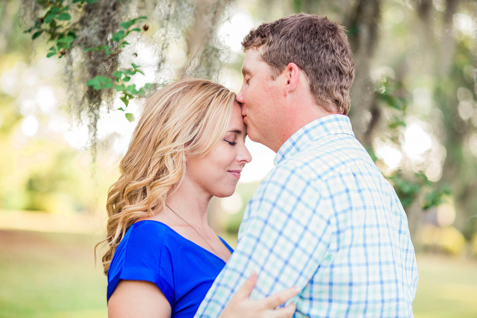 Engaged couple cuddle under a tree with spanish moss, Hampton Park, Charleston Engagement Photography.