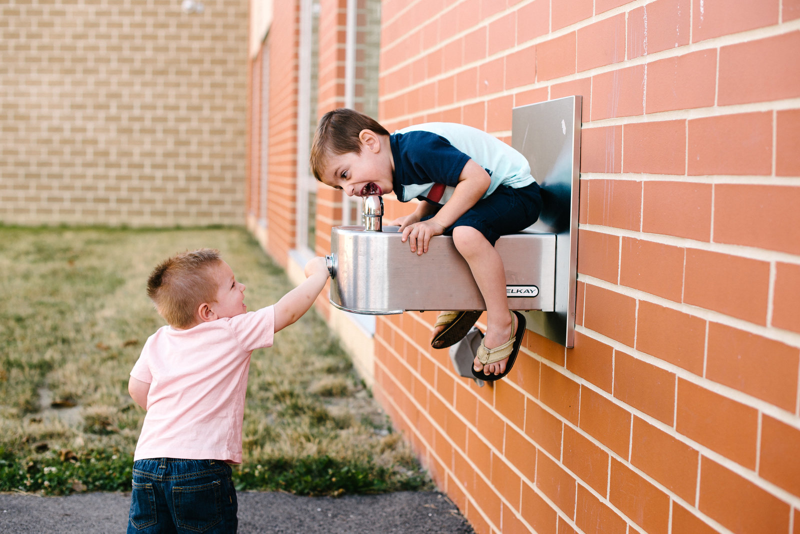 Austintown OH toddler boys drinking from water fountain on playground