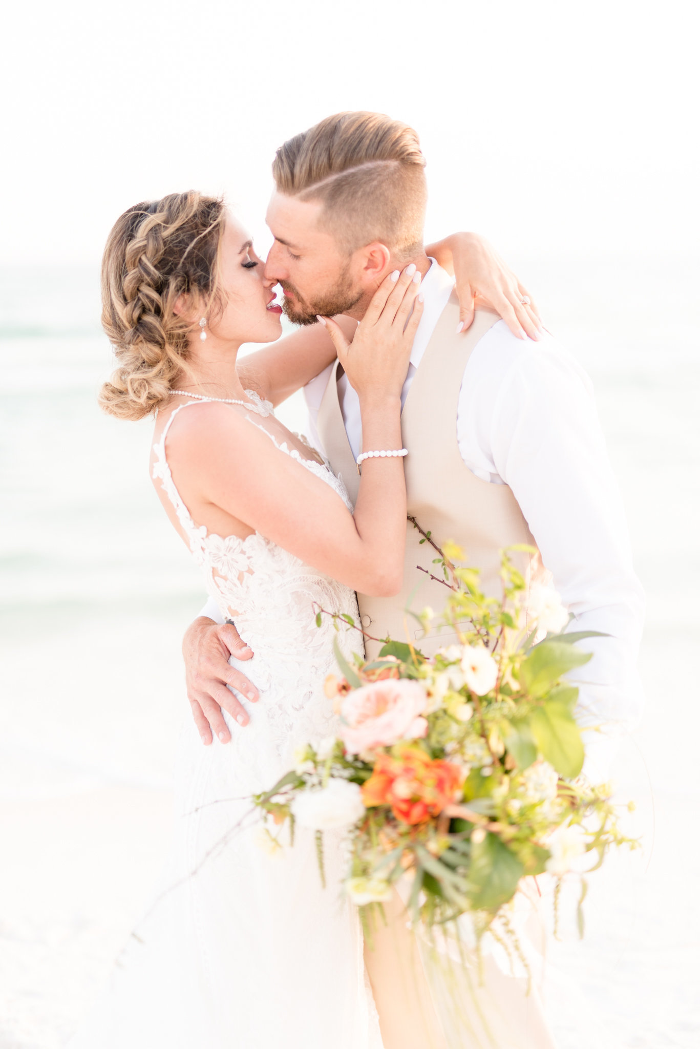 Bride and groom lean in for a kiss on the beach.