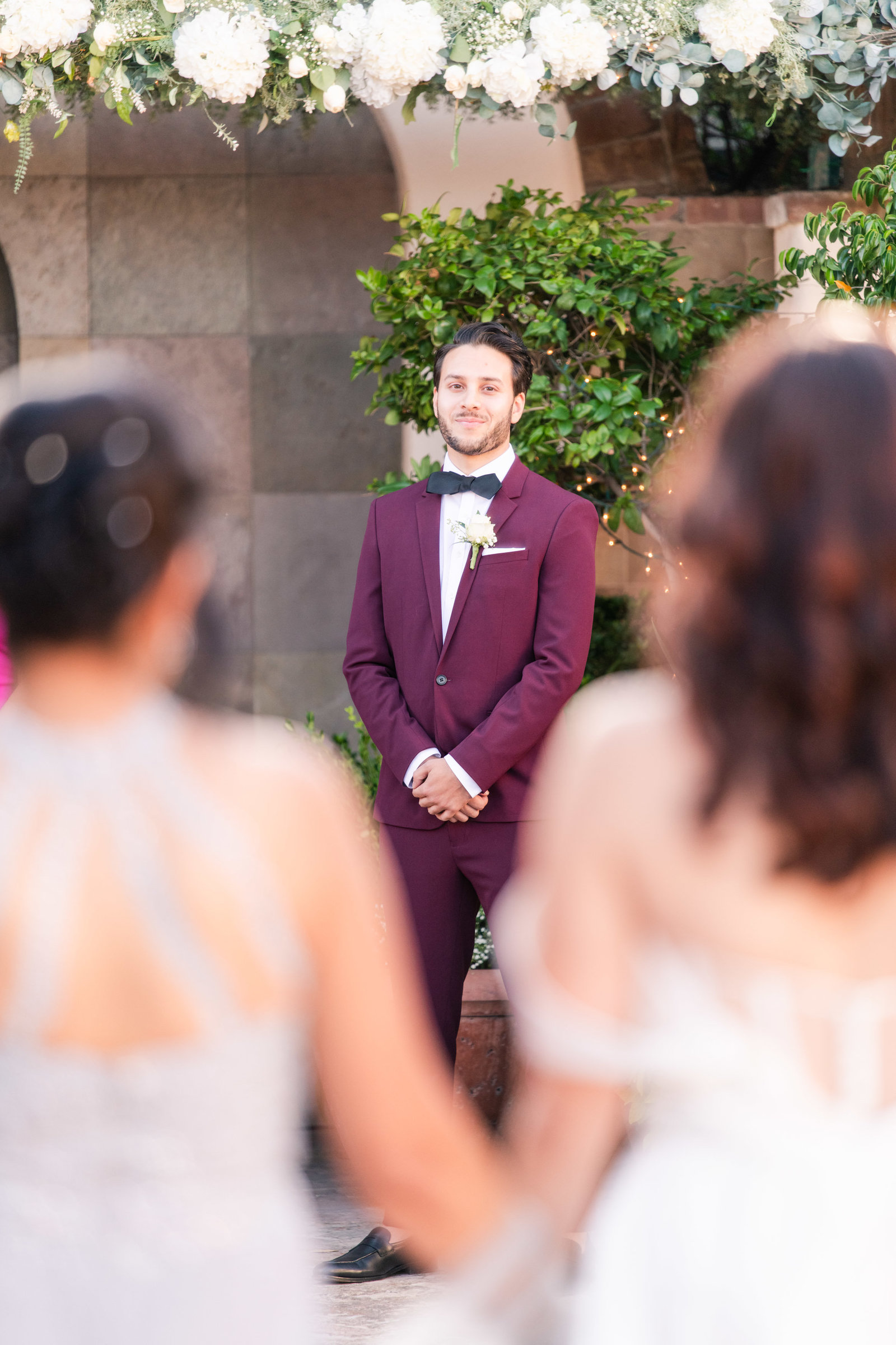 groom watching bride walk down the aisle in the courtyard at Stillwell House