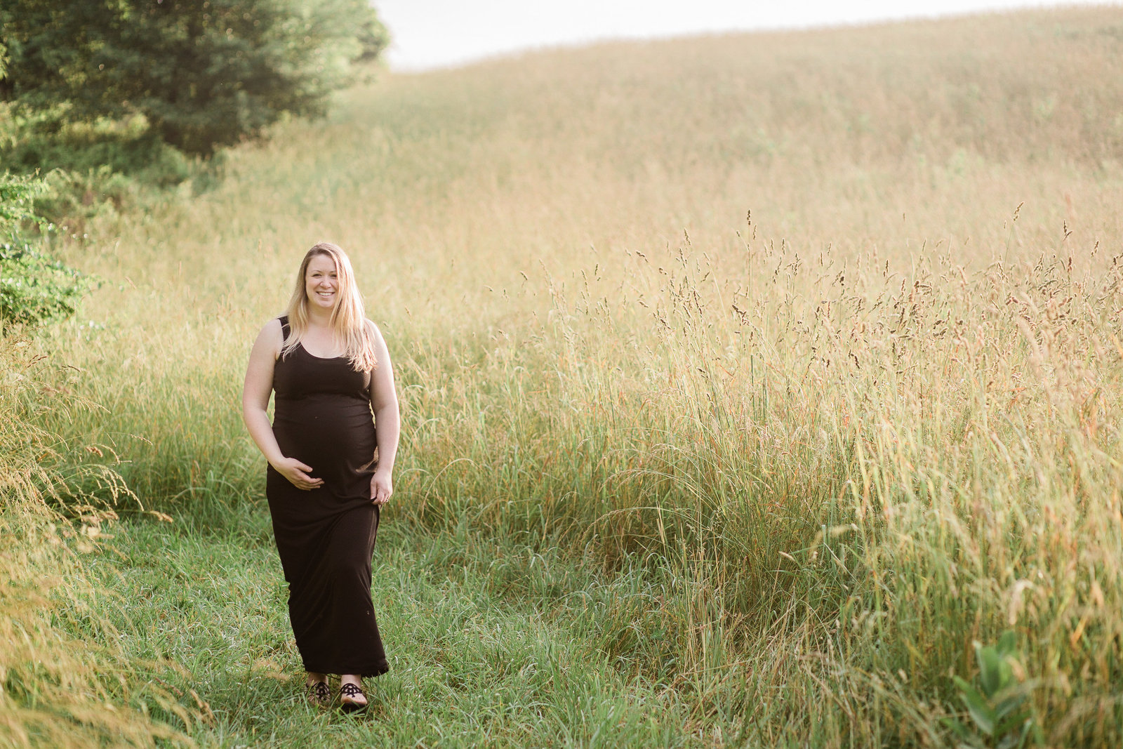 Blonde pregnant mother walking in a golden field in a black maxi dress