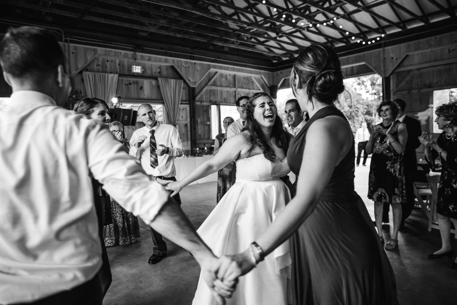couple dances the horah with friends and family during wedding