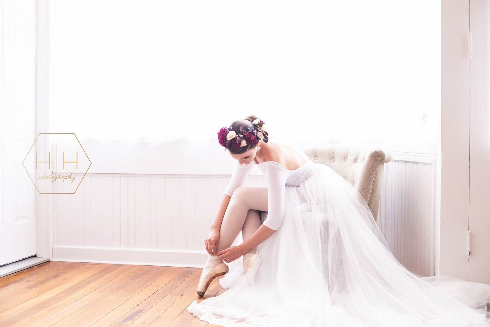 ballerina fixing her pointe shoes with a headwreath