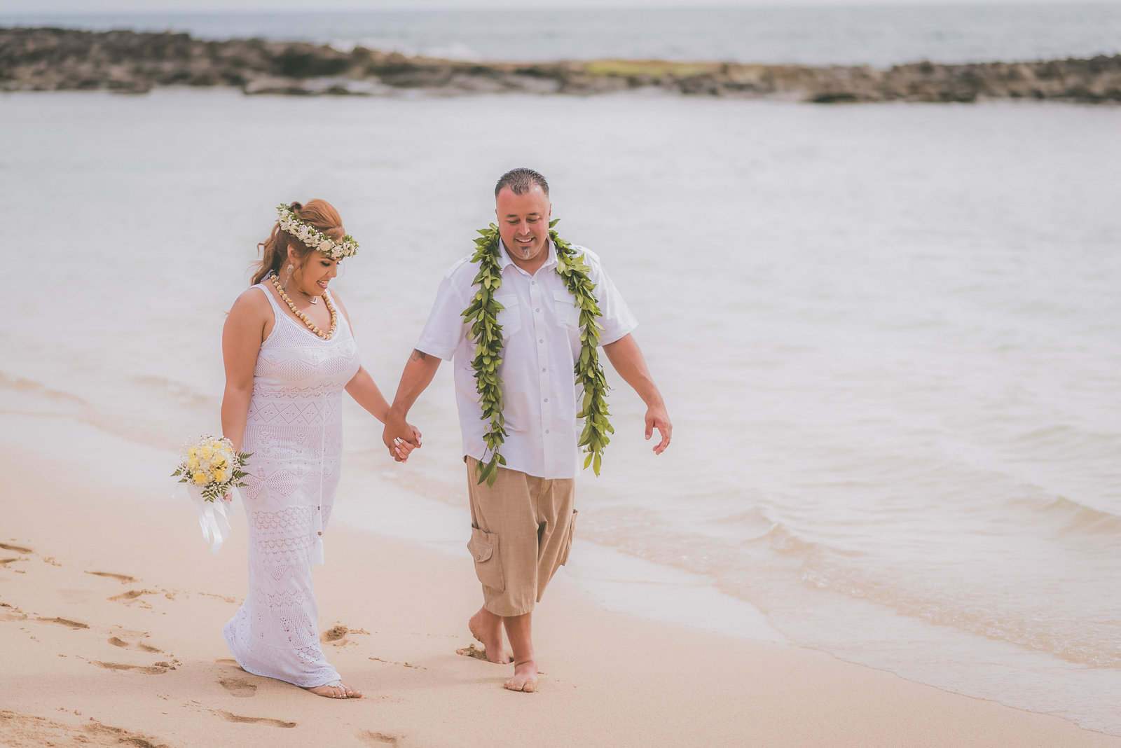 Bride and groom hold hands and walk on Paradise Cove beach in Oahu.
