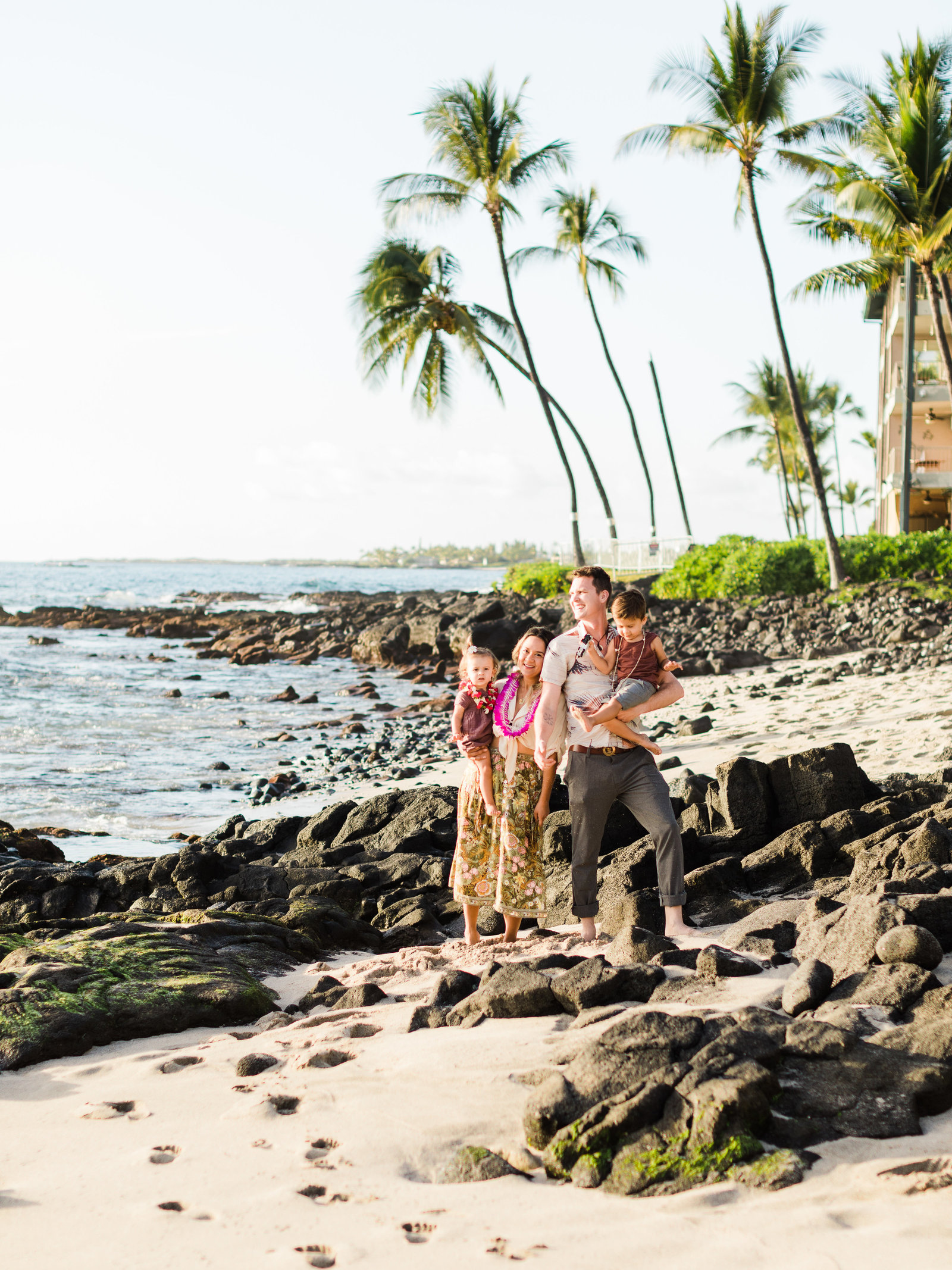 Young couple hold their two young kids on a beach in Hawaii, surrounded by lava rocks and palm trees