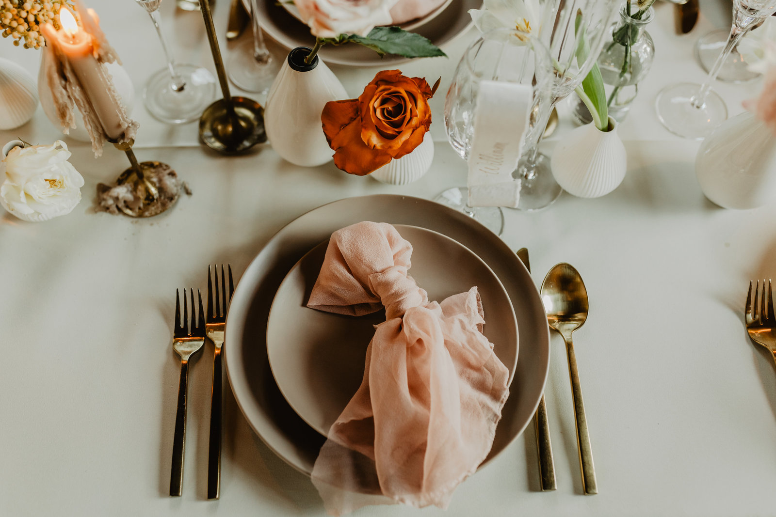 Modern wedding day place settings with blush napkin accent.