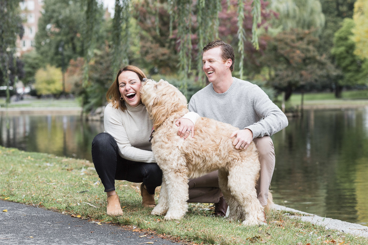 goldendoodle licking woman's face in Boston Public Garden