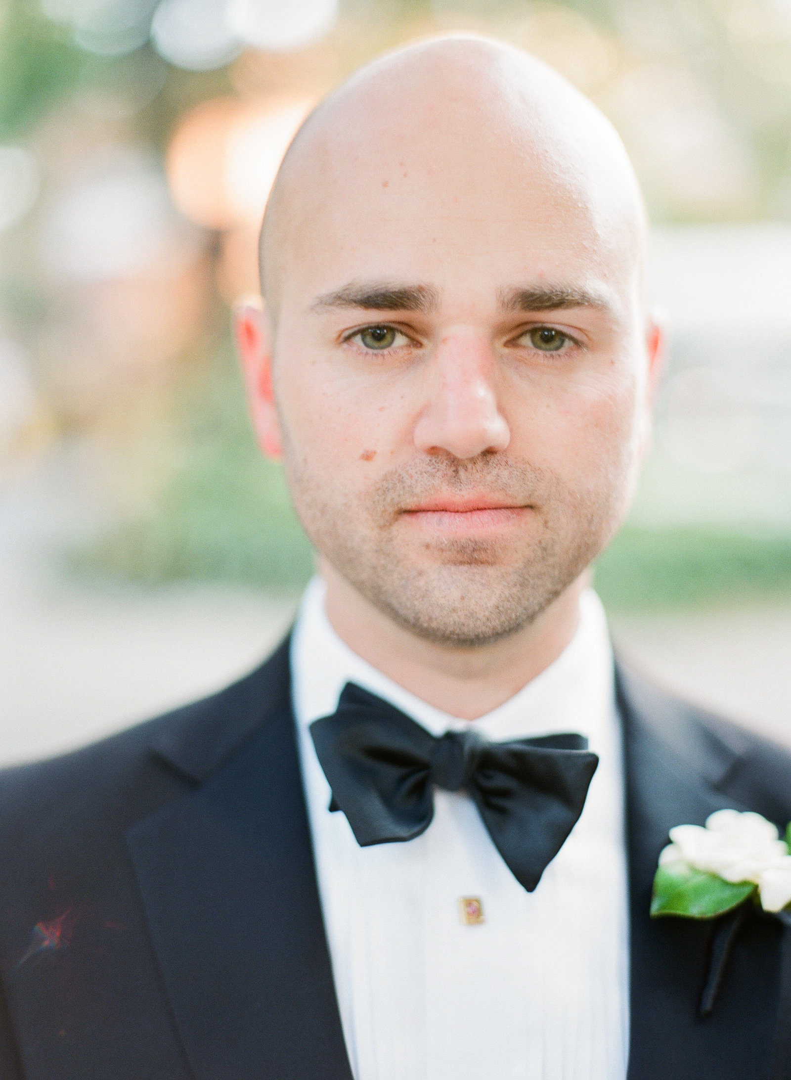 groom in black tuxedo with classic white boutonniere