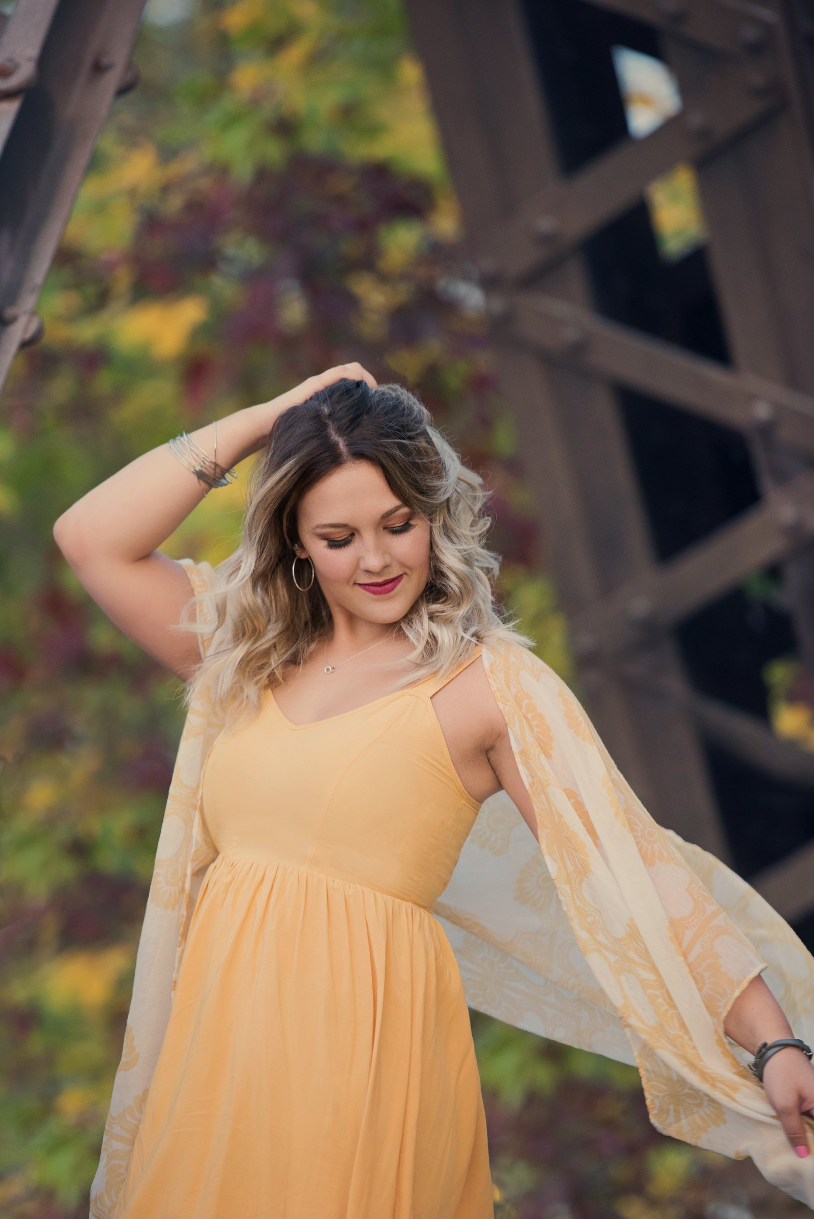 Senior picture of caucasian girl in yellow dress in autumn