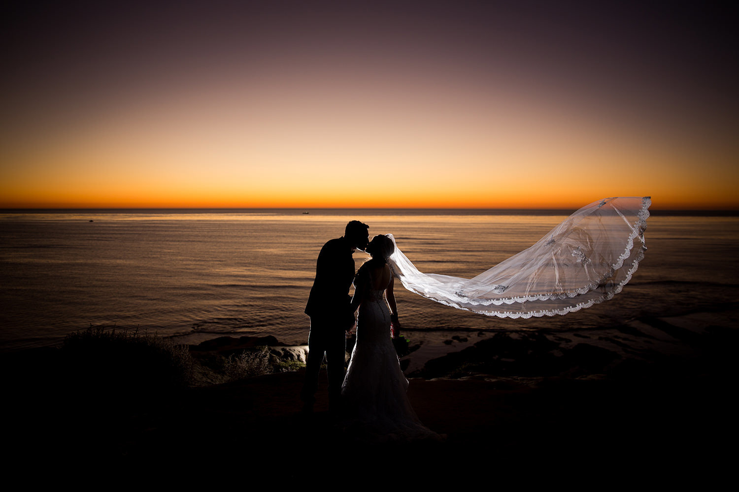 stunning sunset image with long veil on bride