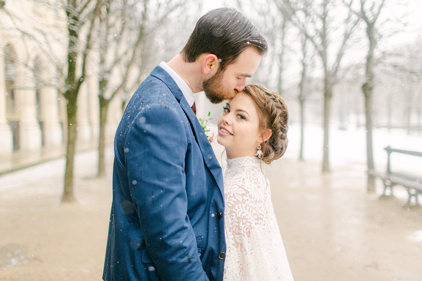 bride looking at camera as the groom kisses her forehead and snow falls around them