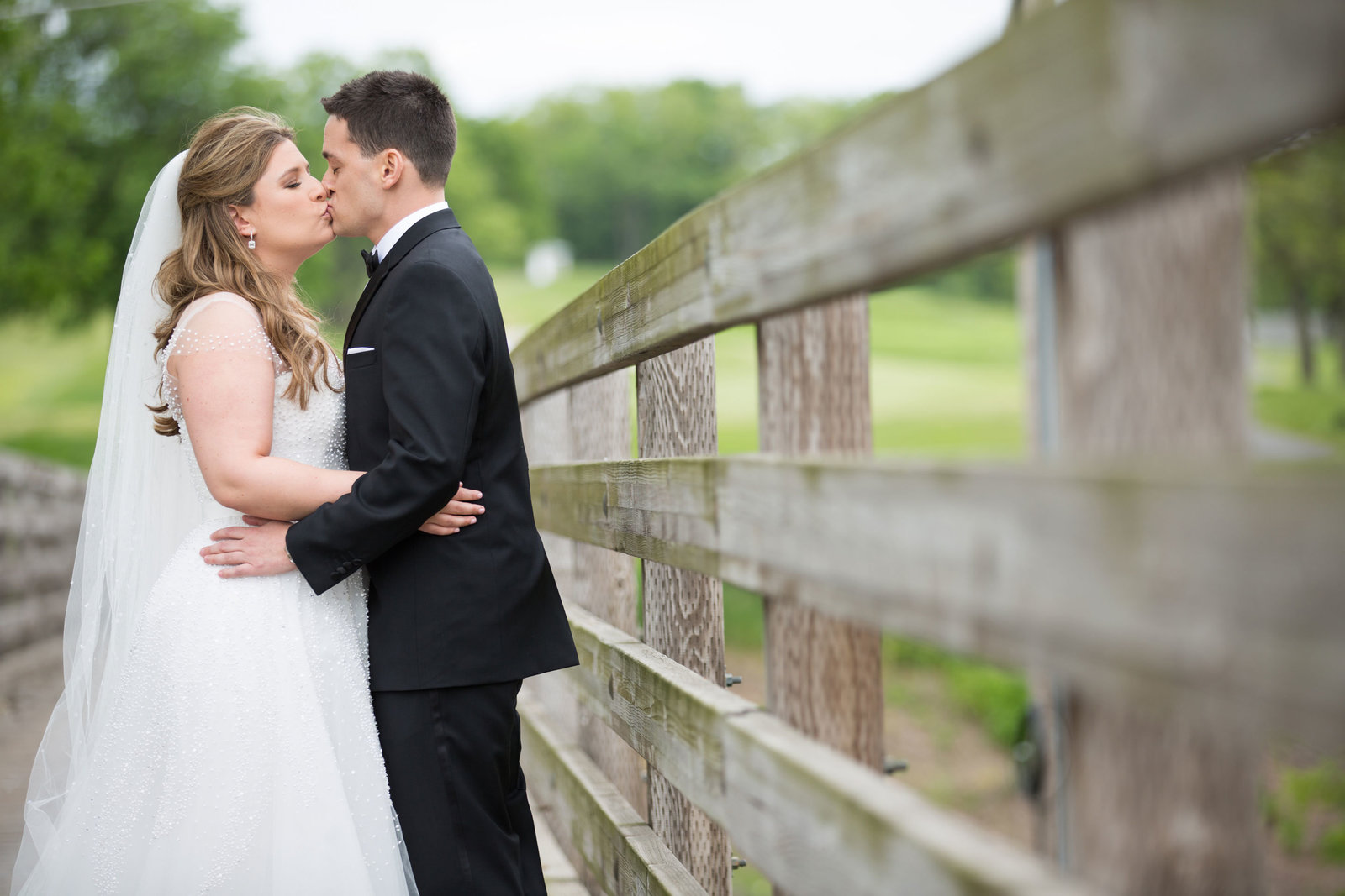 bride and groom kissing on the bridge at Engineers Country Club