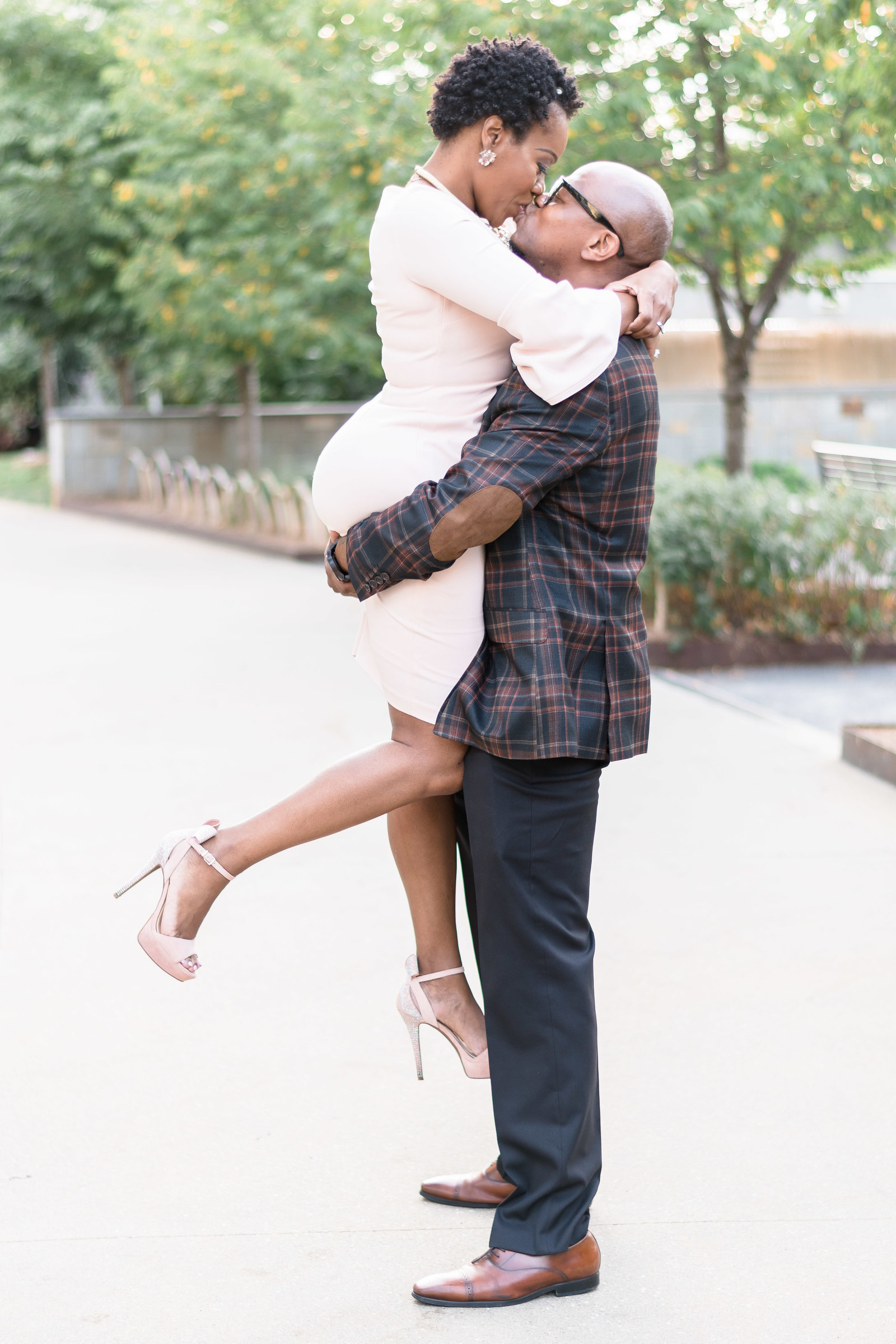 Charlotte, NC engagement photography shot of couple sweep off feet in Romare Bearden Park in uptown charlotte