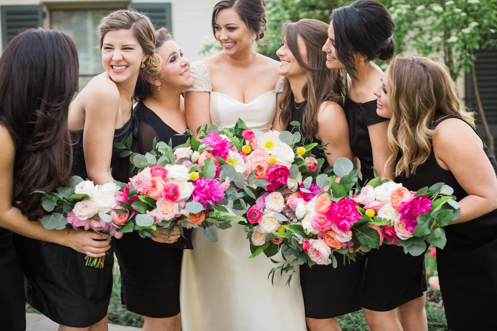 the bride and her bridal party dressed in black with pink florals