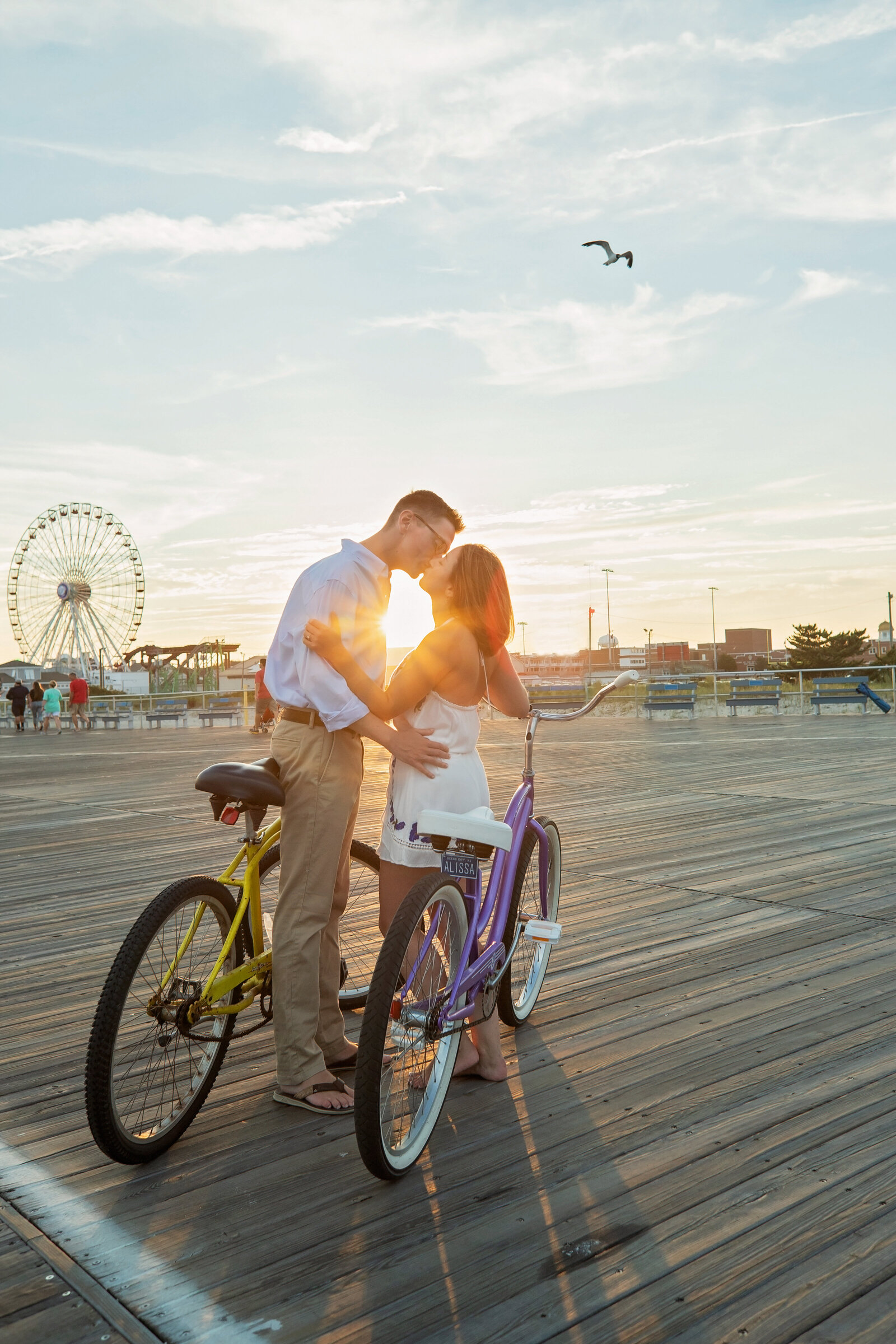 engaged couple biking on boardwalk in Ocean city nj