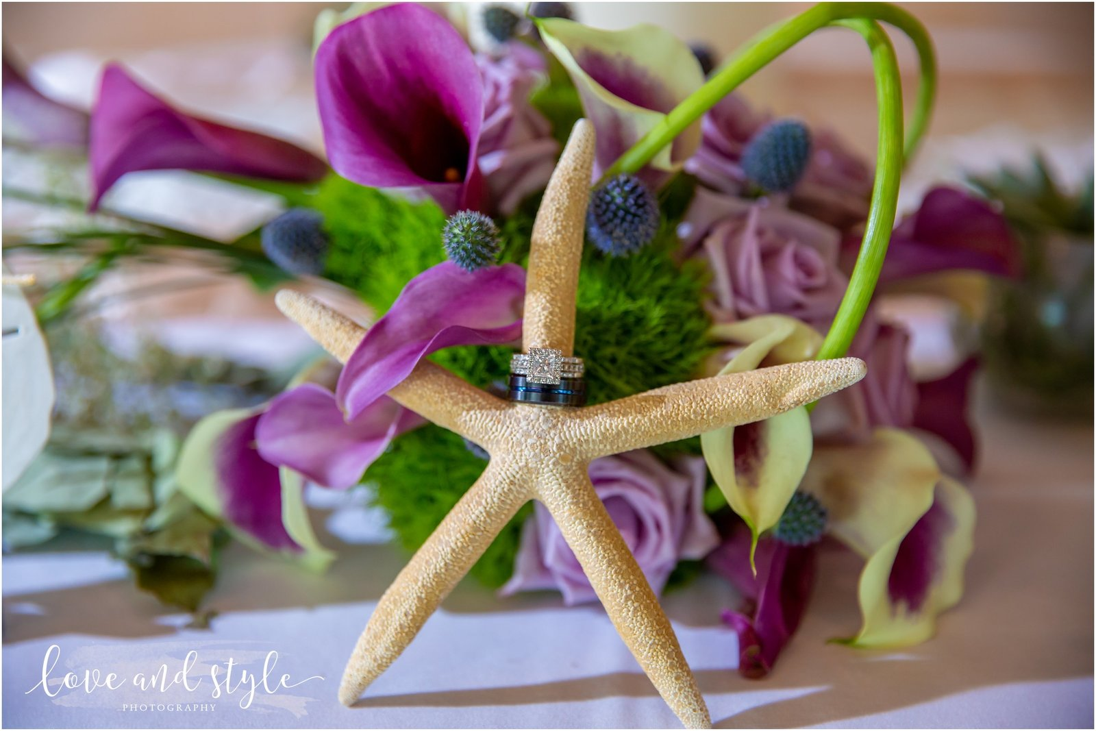 detail shot of wedding rings on a starfish in front of a purple flower bouquet in Sarasota, Florida