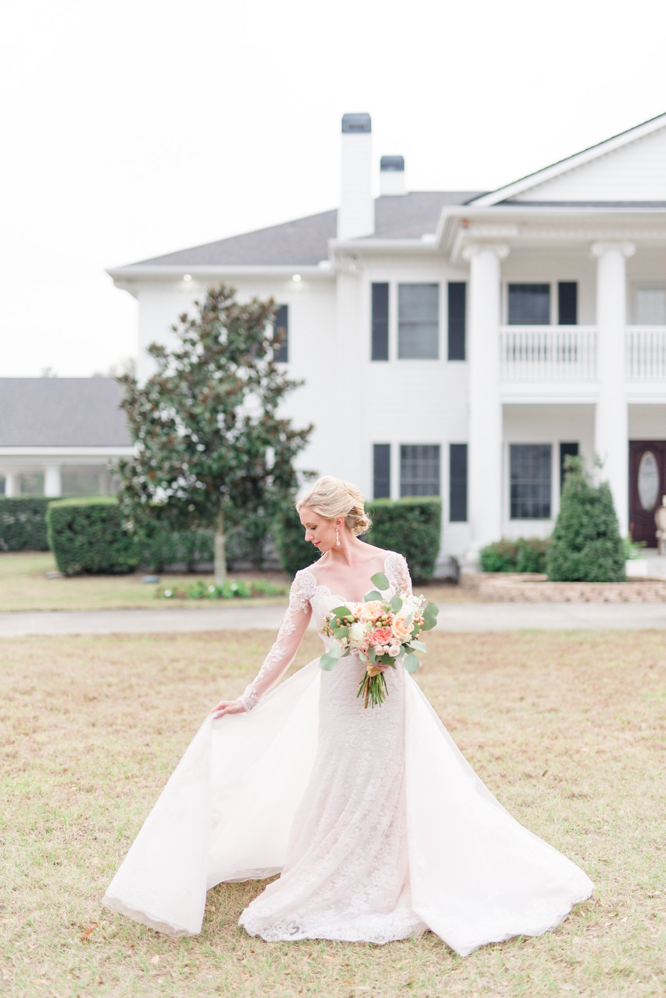 Bride stand in front of white mansion.