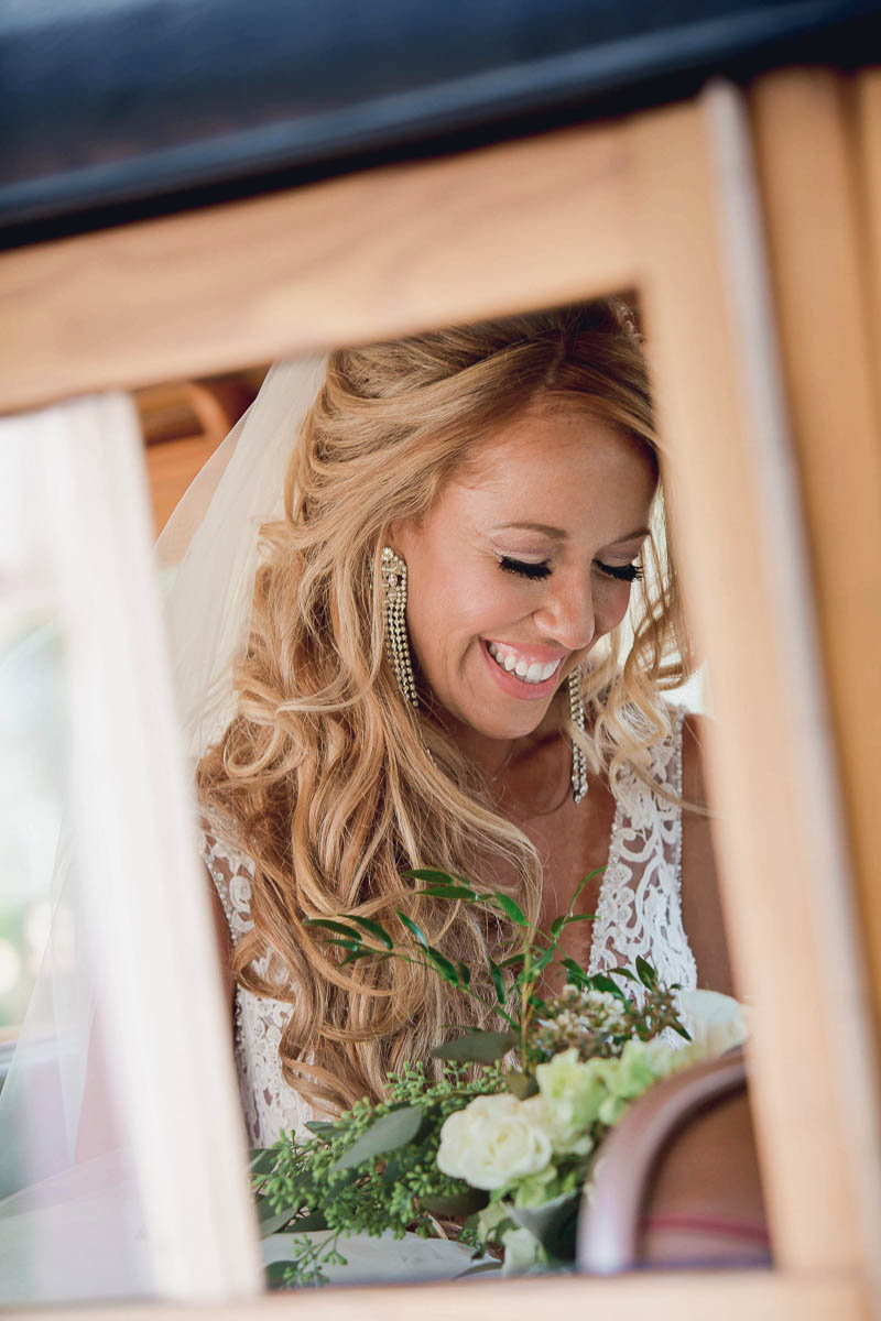 Bride smiles from a window of a vintage car, Destination wedding, Sarasota Garden Club, Florida. Kate Timbers Photography.