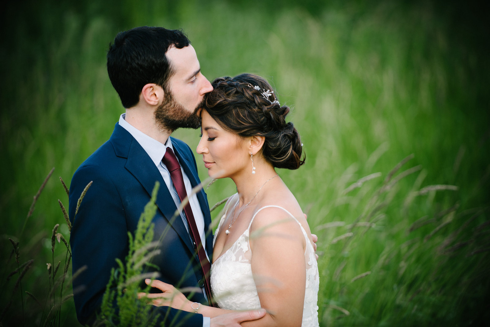 Romantic moment between bride and groom in a field of green