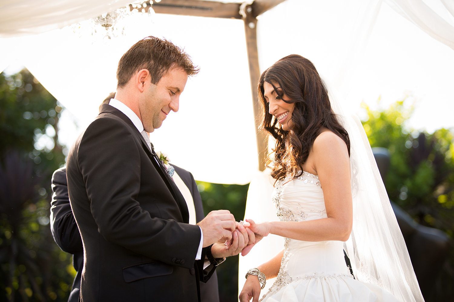 The ring exchange is best captured from closer to the bride and groom