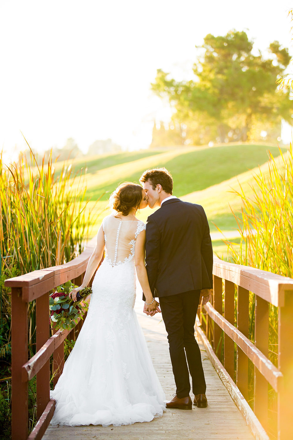 bride and groom on bridge at carlton oaks country club