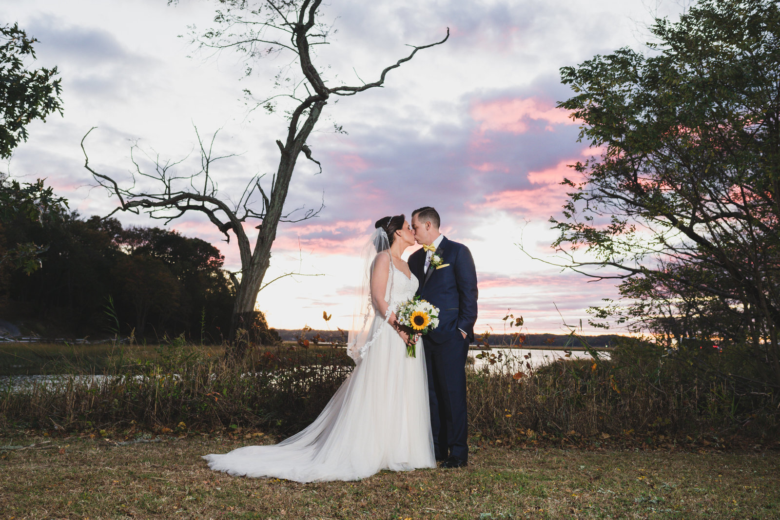 photo of bride and groom kissing near sunset from wedding at Three Village Inn