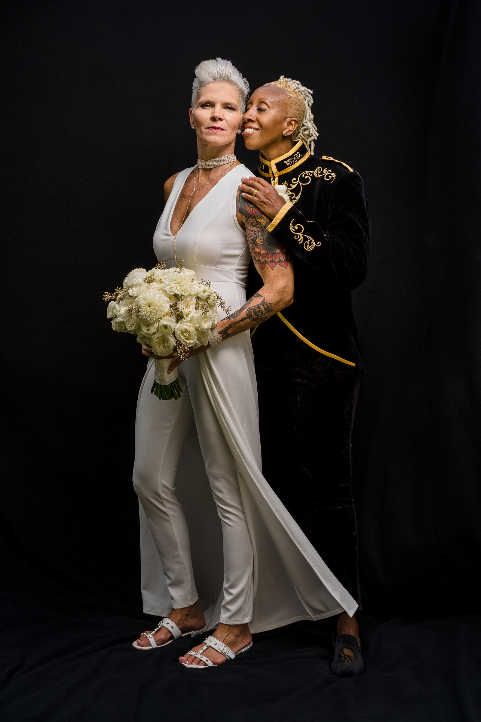 A white and black woman stand cuddled on their wedding day for a portrait in front of a black backdrop