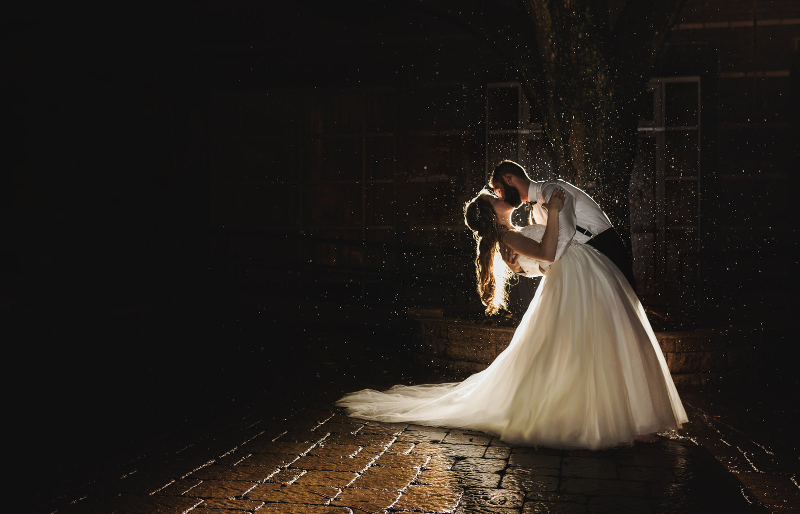 charlotte wedding photographer jamie lucido with bride and groom in the evening with beautiful rain frozen around them as they kiss
