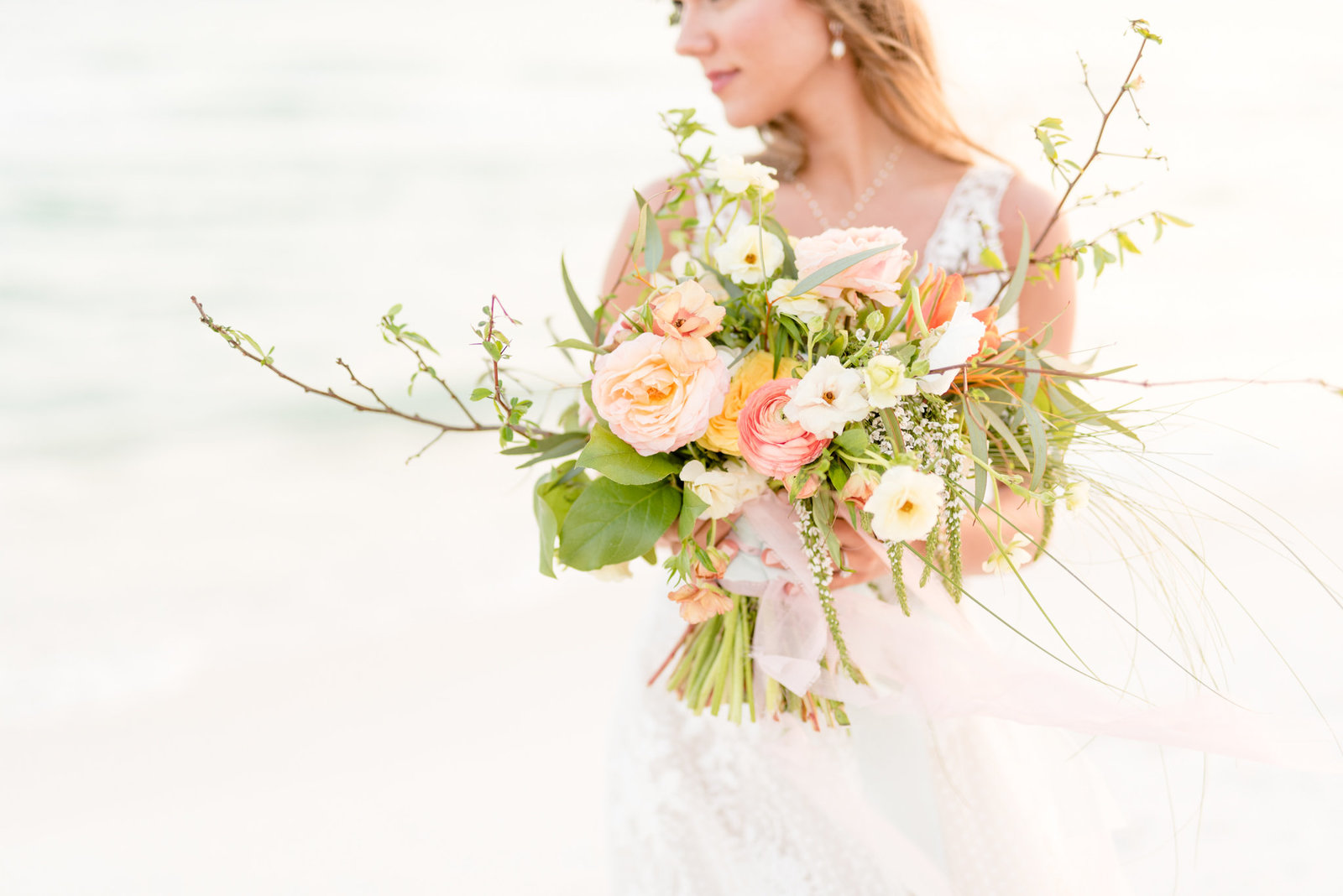Bride holds bouquet on clearwater beach.