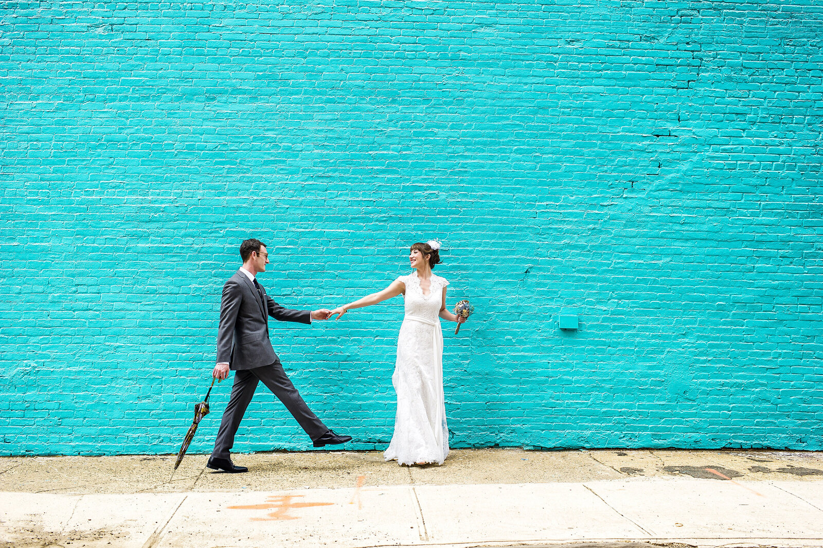 Couple strolling down the street holding hands in front of a lite blue wall in Brooklyn.