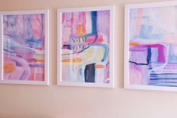 Three white framed pieces of colorful abstract art.