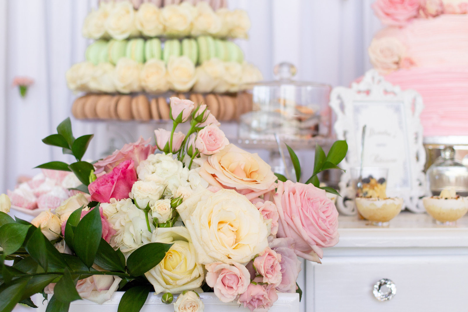 Bright pinks, whites and green flowers in high-end white dress with desserts in background at reception on wedding day
