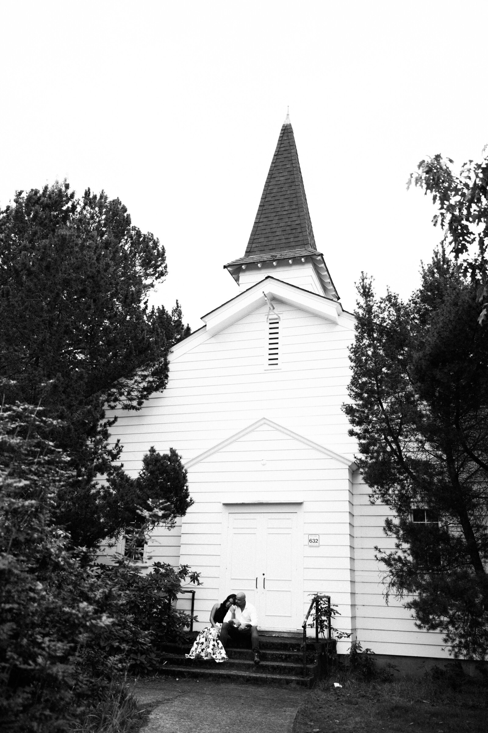 Cute church behind couple at engagement session, in Discovery Park, the best place for romantic engagement photos in Seattle