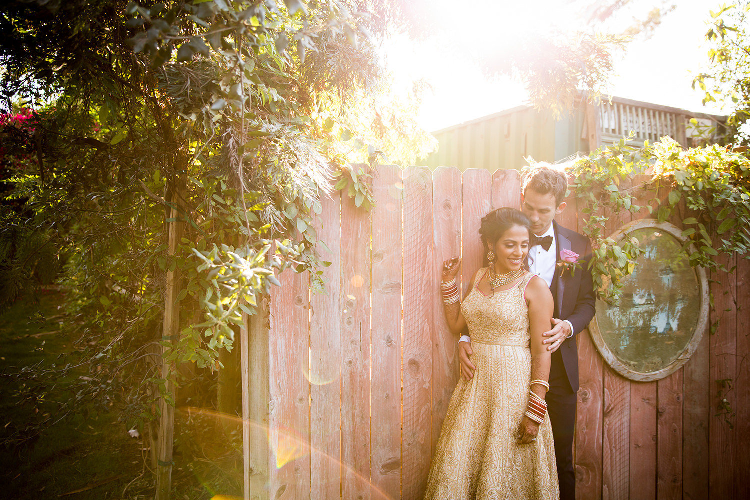 Romantic portrait with lens flare in front of an old fence.