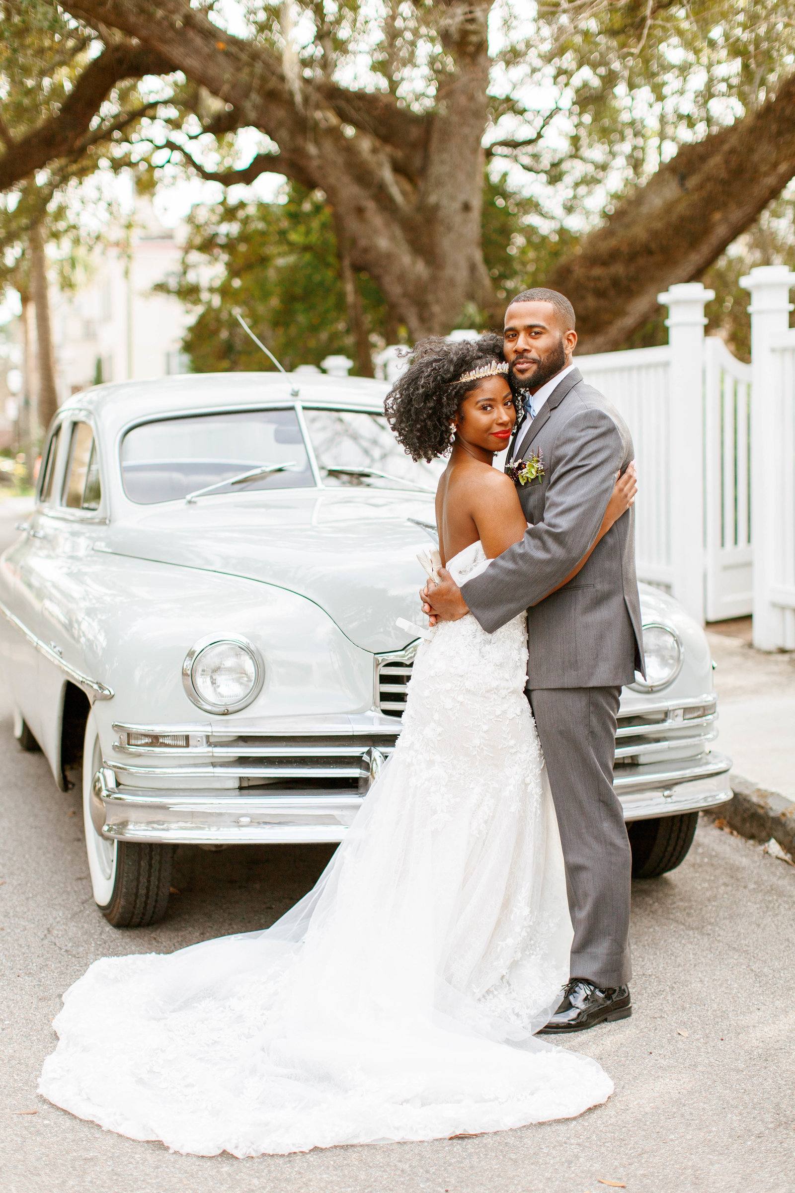 Classic luxury wedding couple in front of a classic getaway car