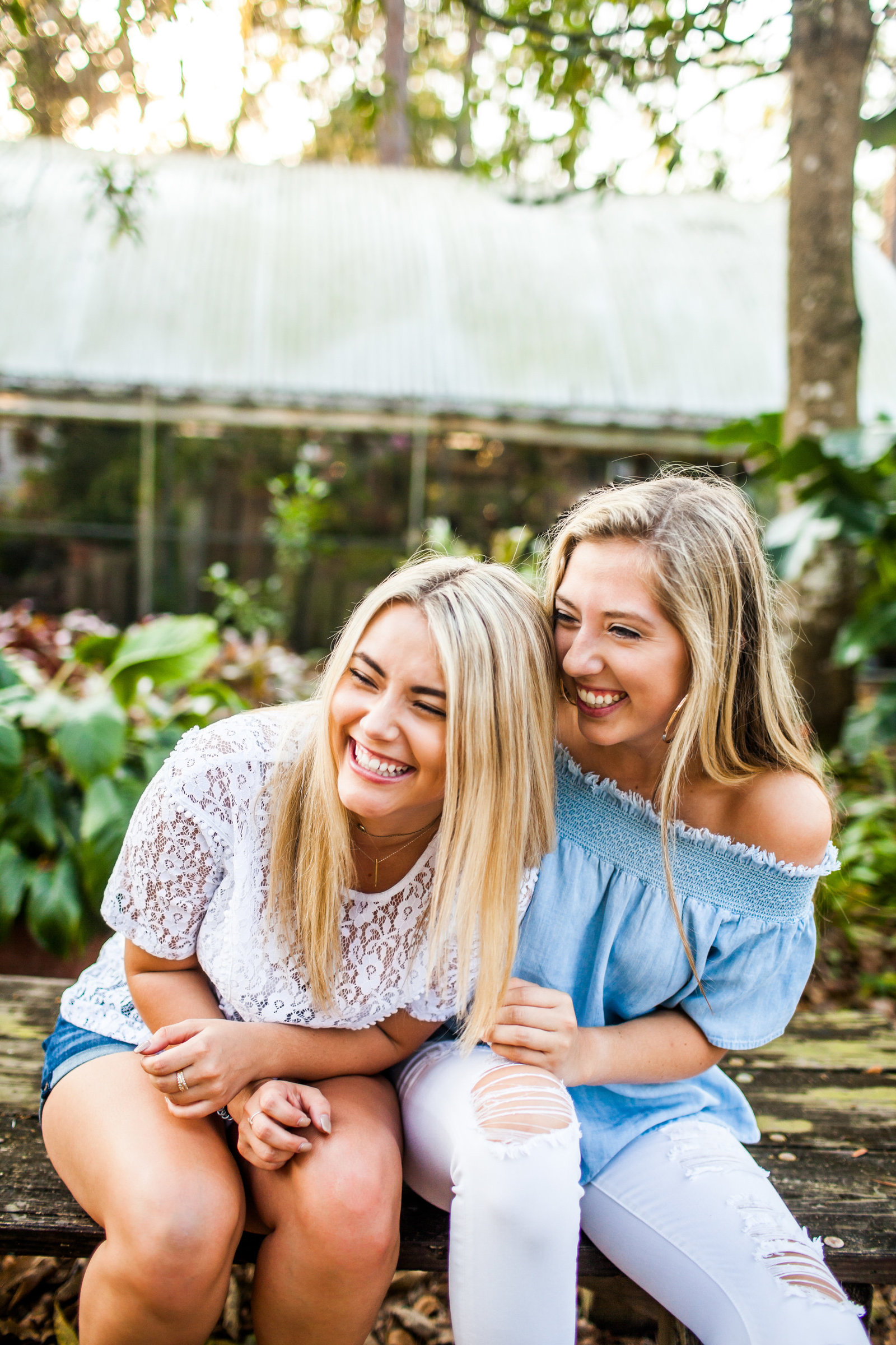 Friends laughing on a bench in a lush Florida garden
