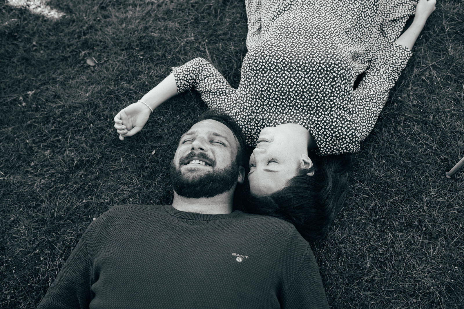 Natural photograph of relaxed couple laughing and cuddling outside laying in the grass in the Suffolk countryside
