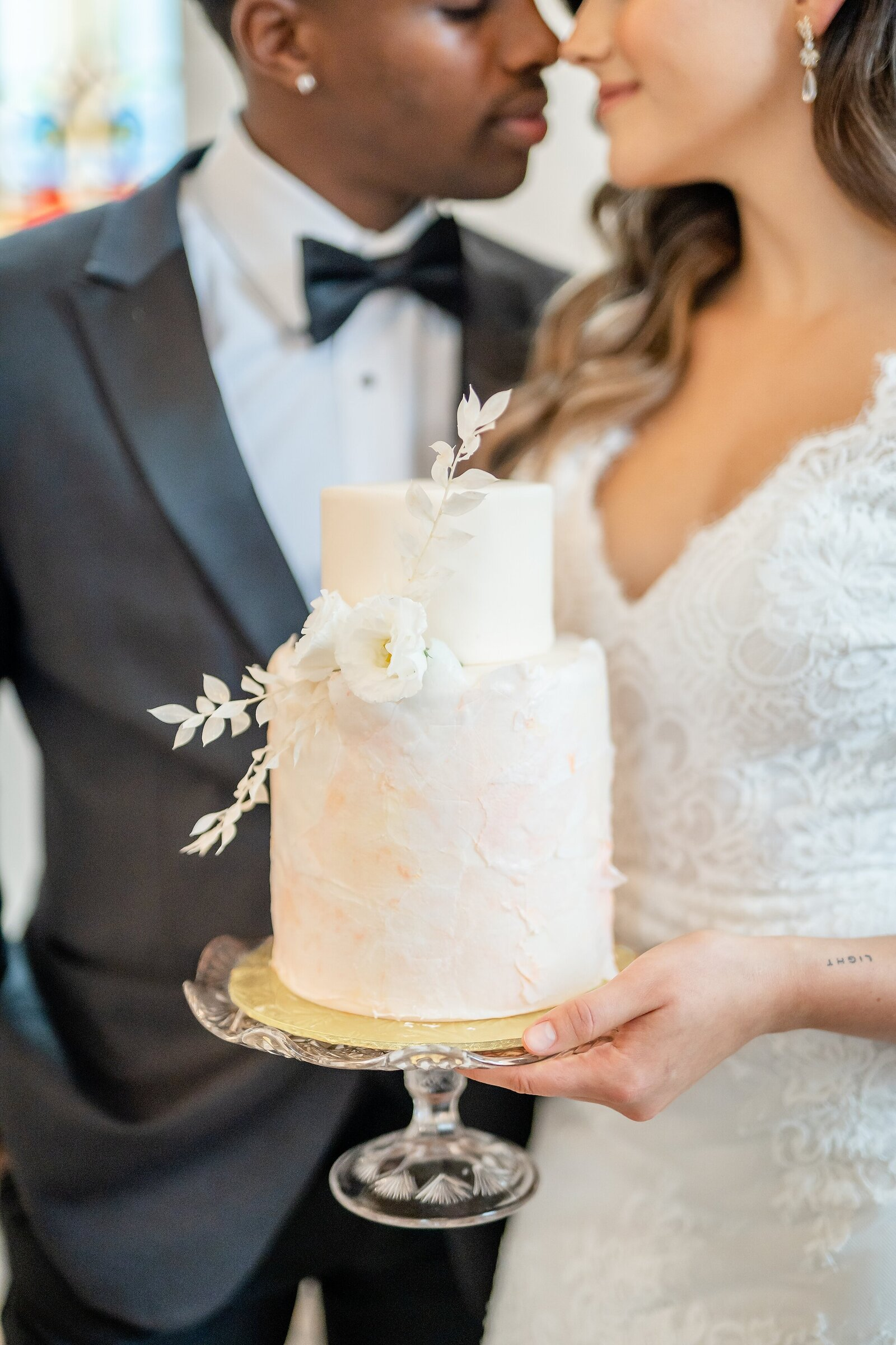 Couple-holding-a-blush-2-tiered-wedding-cake-at-La-Petite-Chapelle