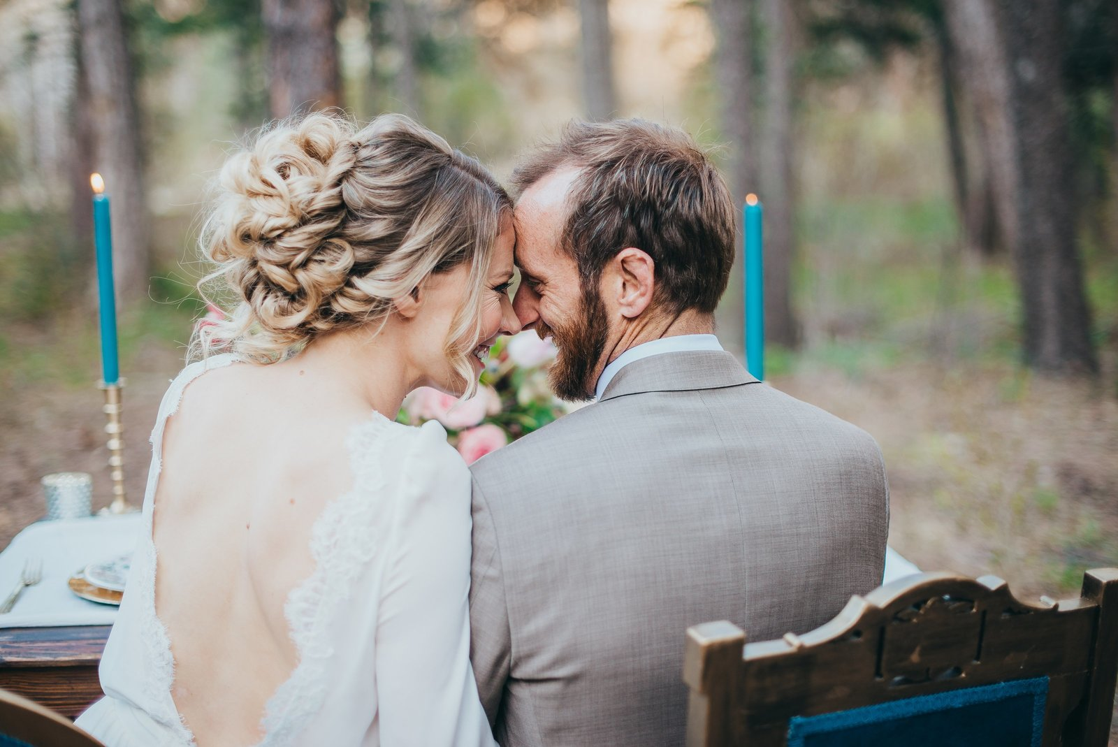 Couple sitting at a reception table for an adventurous wedding in the woods