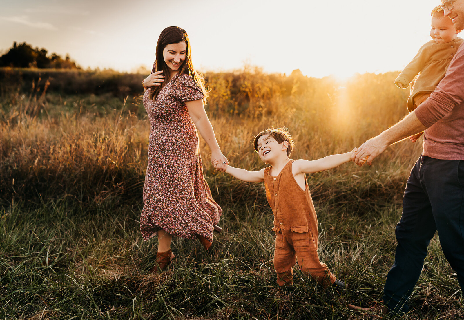 family walking through field at sunset