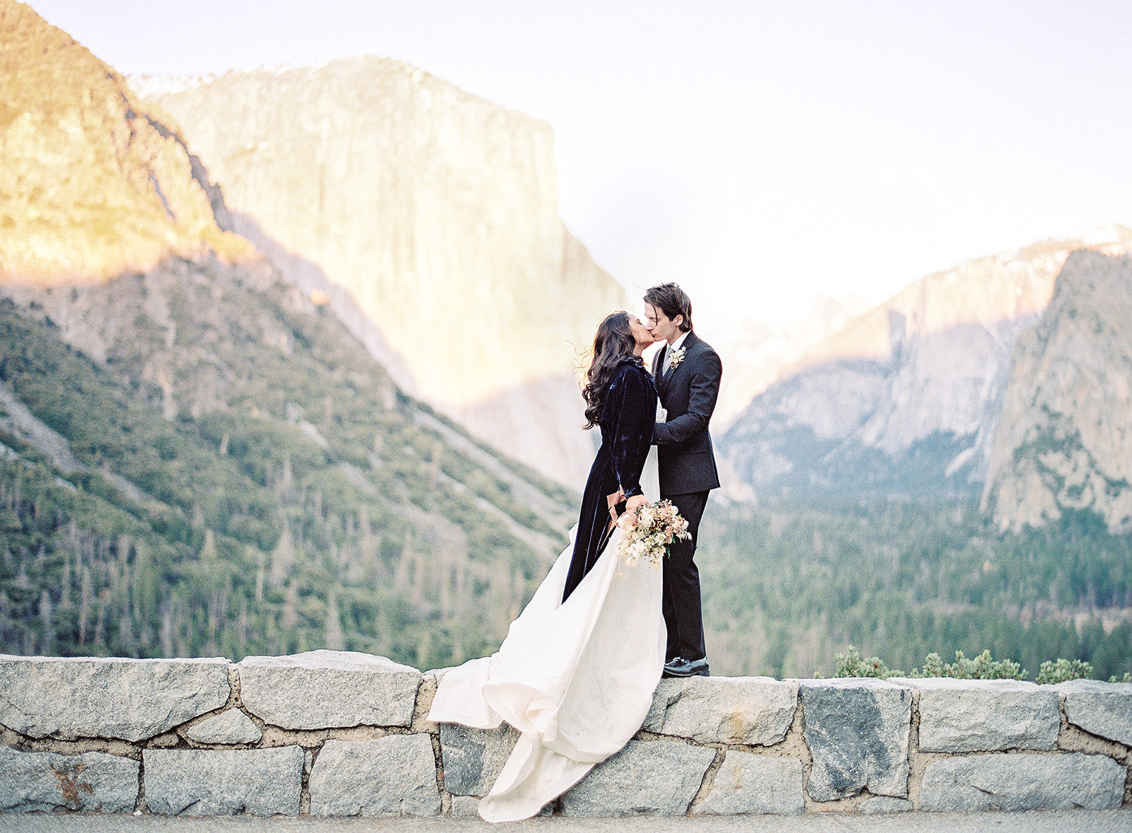 Bride and groom at the edge of a peak in Yosemite National Park. Bride in velvet blue coat Photographed by Amy Mulder Photography