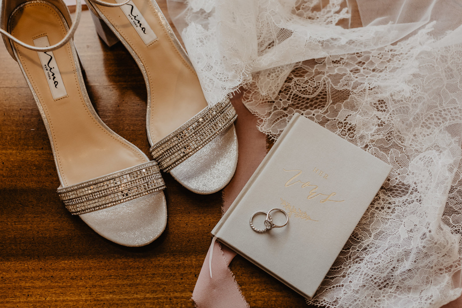 Bridal details complete with rings, vow book and wedding shoes with veil lace accent at Saddle Woods Farm.