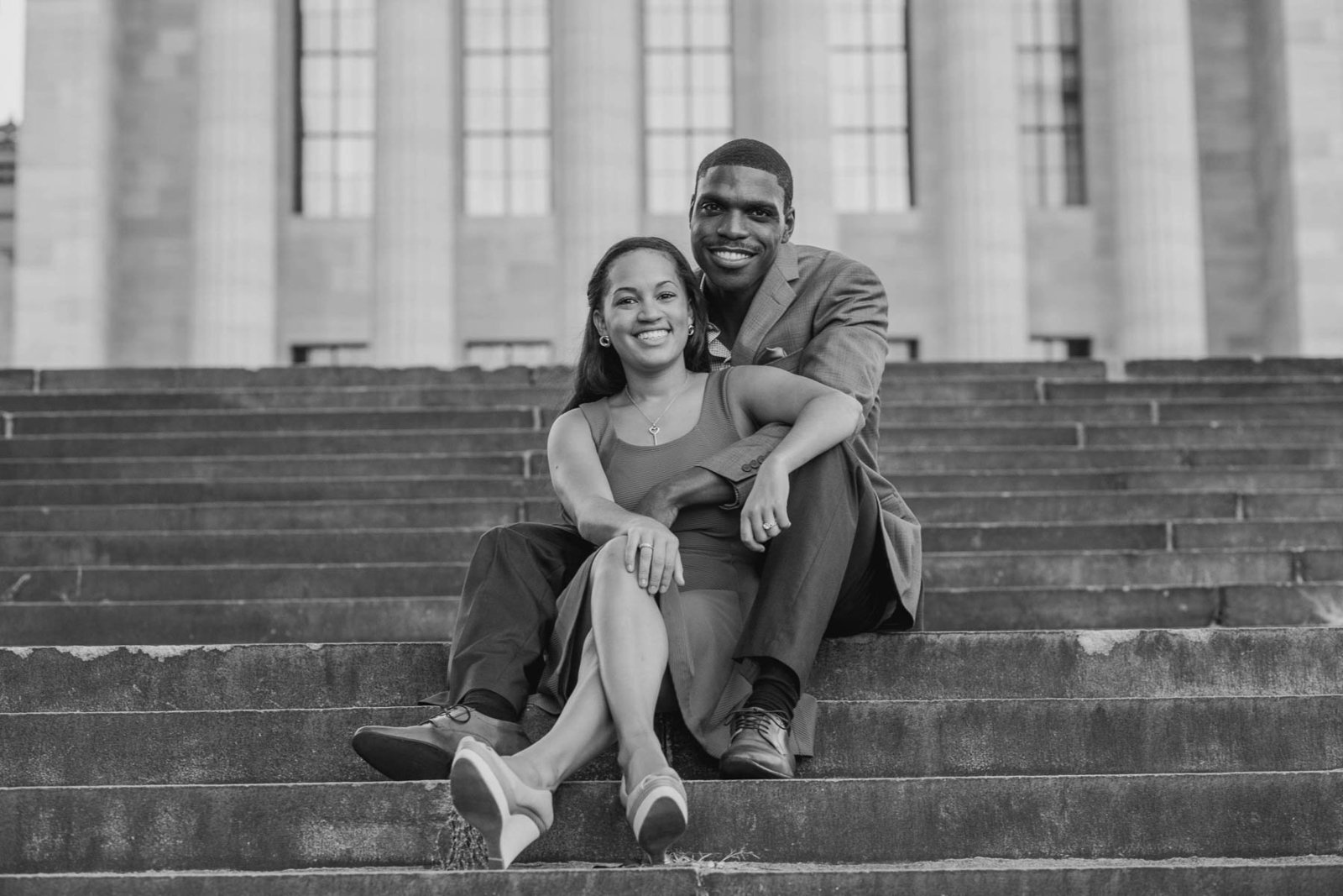 Engaged couple sitting on the steps of the art museum, Philadelphia, Pennsylvania