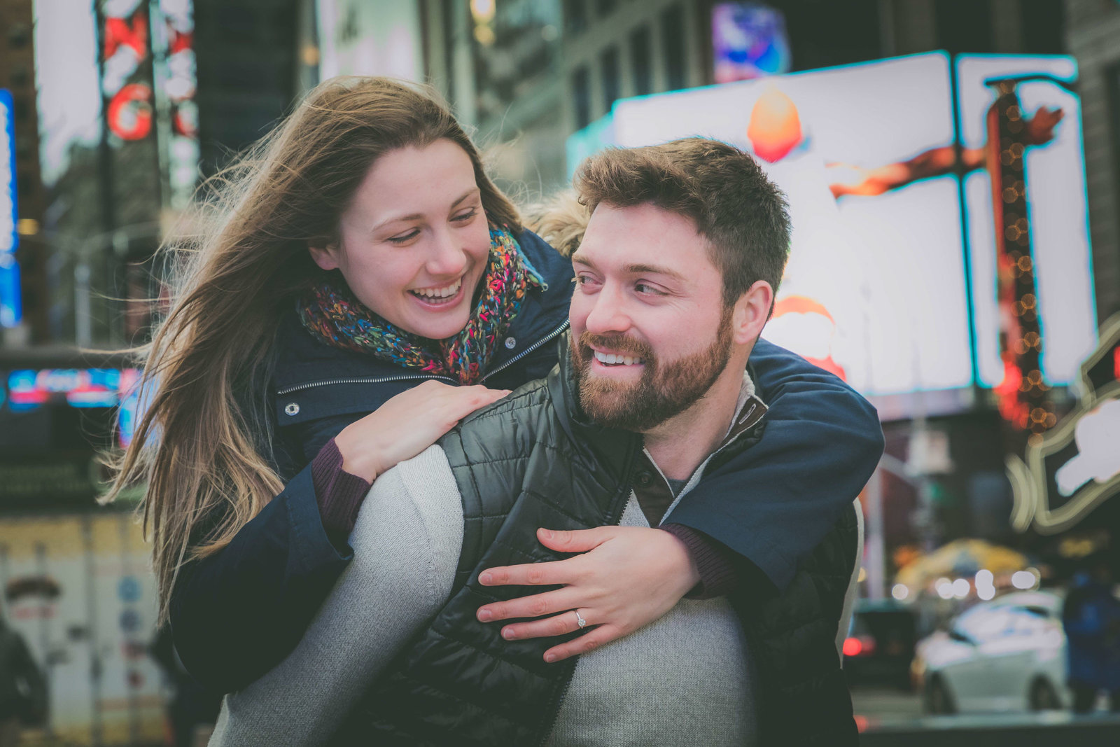 Couple piggybacks during Times Square NY engagement.