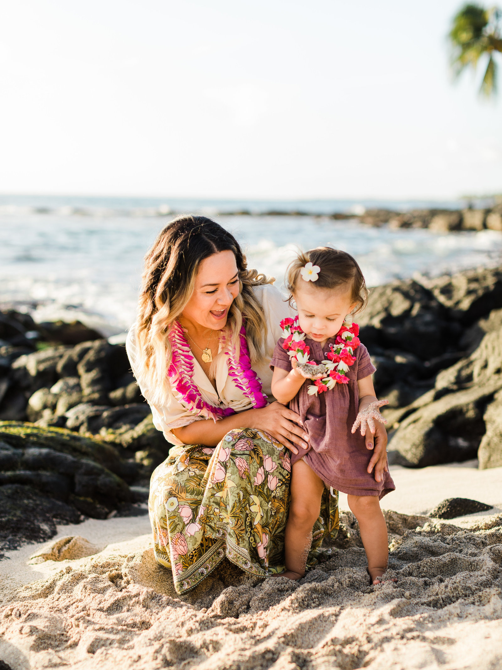 Young mother holds her young daughter on a beach in Hawaii, surrounded by lava rocks and palm trees. They wear tropical patterns and leis.