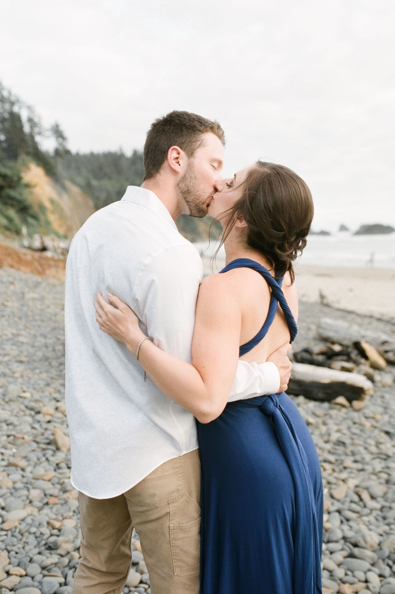 Engaged couple kisses on Oregon coast beach